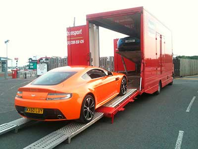 Aston Martin loading into multiple covered car transporter